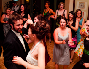 Ally and Anthony, bride and groom, dance surrounded by happy guests.