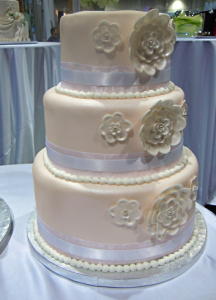 cream wedding cake with flowers and white ribbon