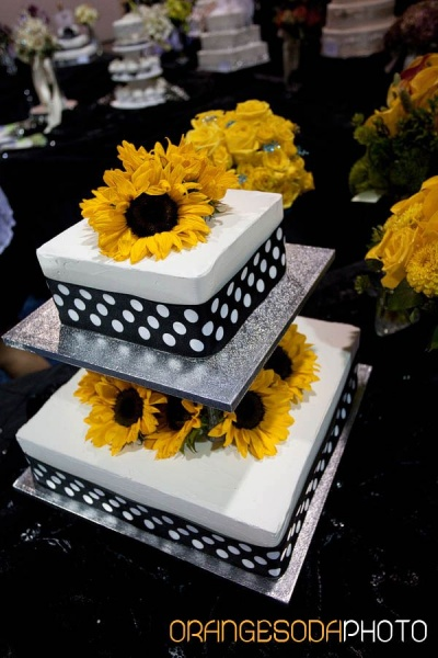 white pedastal cake with black and white polka dot ribbon, fresh sunflowers
