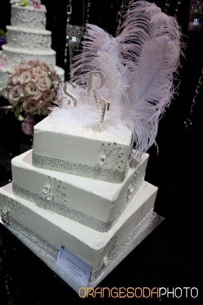 square white cake with sparkling band around each tier, monogram topper with light pink feathers