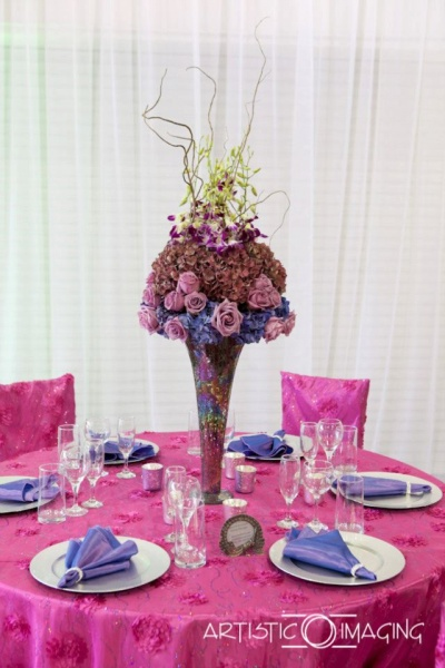 reception table with pink linens, silver plates, purple napkins, tall centerpiece