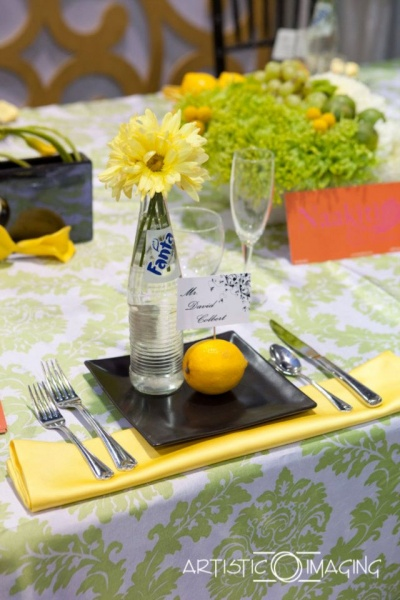 reception table with lemon and lime colors, black plates, Fanta bottle with daisies