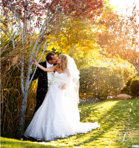 Bride and Groom kiss in autumn wedding