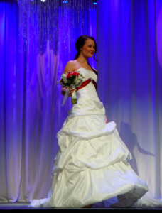 bride in white gown with red sash at fashion show