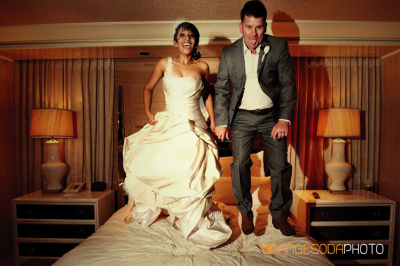 Bride in ivory gown and groom in gray suit with brown shoes jump on a bed
