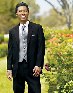 Man in black pinstripe tuxedo, unbuttoned, with gray vest and tie