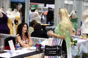bride speaks to vendor at bridal show booth