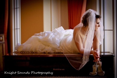 bride lying atop piano