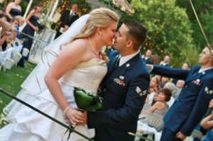 bride and military groom kiss