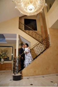 bride and groom on wrought-iron stair case
