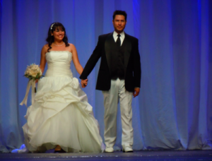 bride and groom holding hands at fashion show