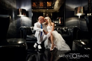 excellent lighting: bride and groom, both wearing white, sit on black couch