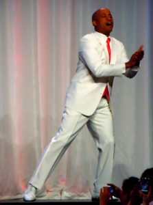 excited groom in a white suit, white shoes, and bright pink tie