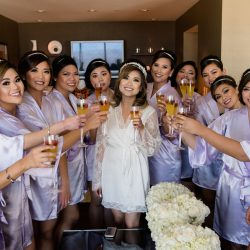 Bride Erica and her bridesmaids wearing fun satin robes and drinking champagne
