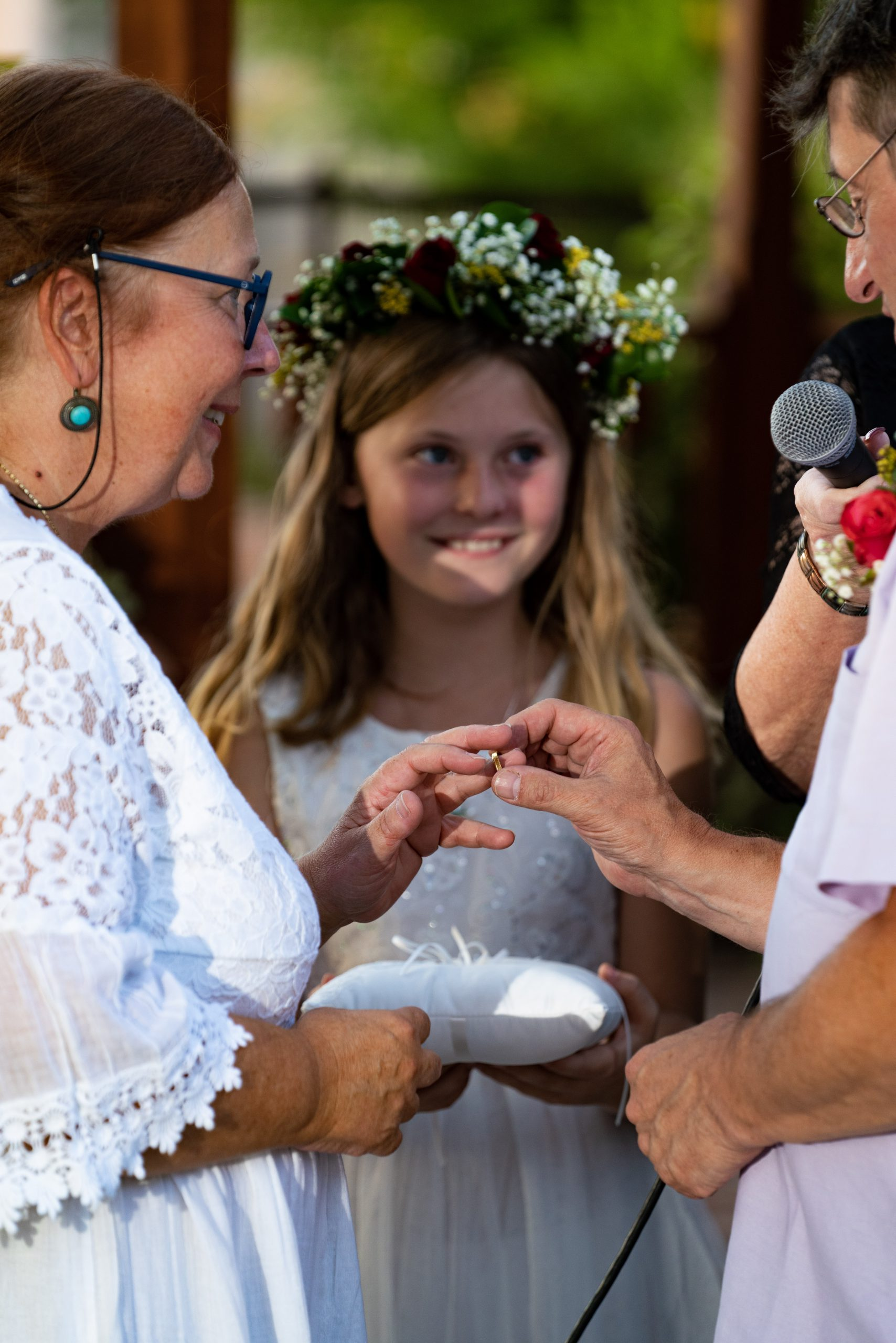 Groom puts the ring on bride with flower girl watching Bridal Spectacular Las Vegas